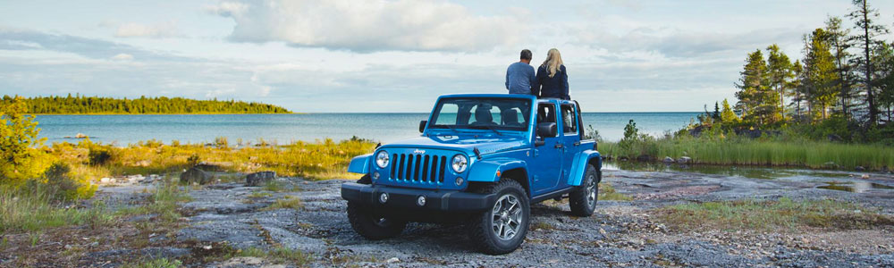 Blue Rent-a-Jeep parked near lake