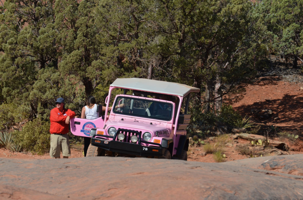 Riders exiting a Pink Jeep