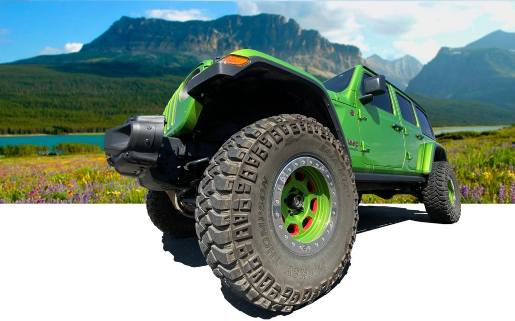 Green Jeep Wrangler in a meadow